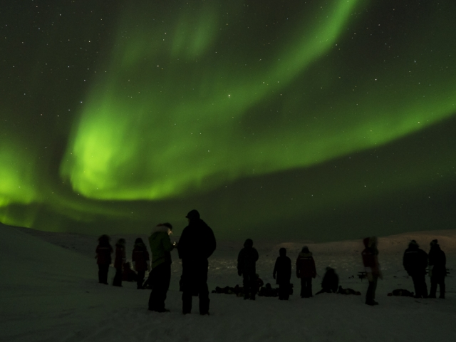 Researchers watching the Northern Lights in Apex, Nunavut, Canada
